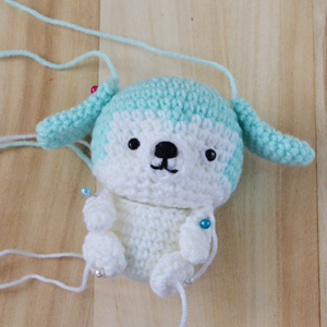 attaching limbs and ears of amigurumi puppy